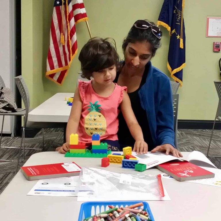 girl and mother play with toys at the library