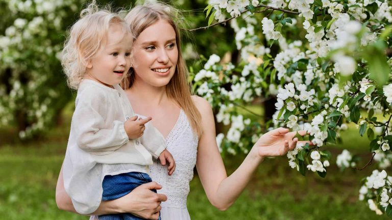 mother holding daughter looking at flowers